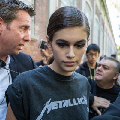 Kaia Gerber, wearing a black Metallica tee shirt, walks through a flock of reporters