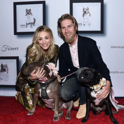 Kaley Cuoco in a gold pantsuit poses with Karl Cook in a suit and two pitbulls