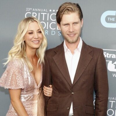 Kaley Cuoco smiling in a pink dress holding hands with husband Karl Cook in a brown suit