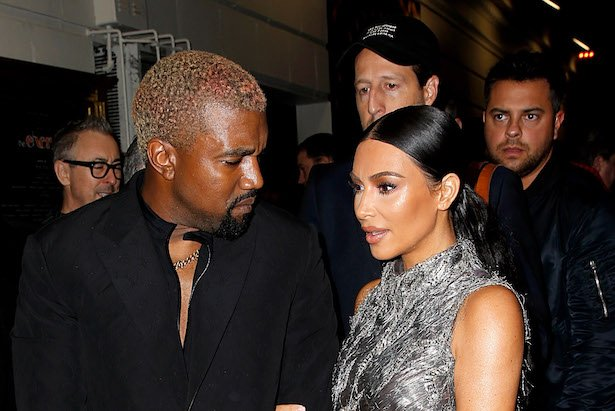 Kanye West in a black suit with blonde hair looks at Kim Kardashian in a silver dress