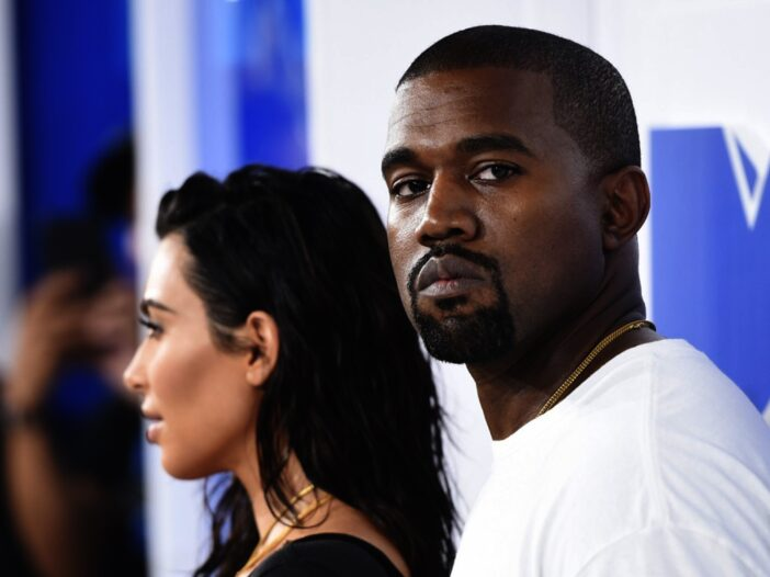 Kanye West looking upset and staring off in the distance with Kim Kardashian in the background looking at the cameras at a recent red carpet event.