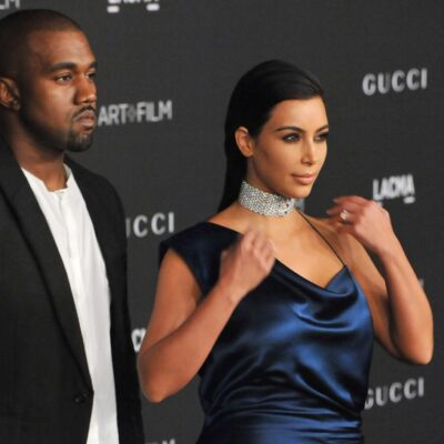 Kanye West wearing a black suit stands with Kim Kardashian, in a blue dress at an art and film gala