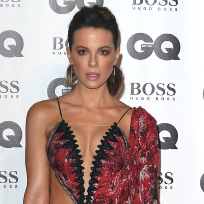 Kate Beckinsale in a red and black dress in front of a white background