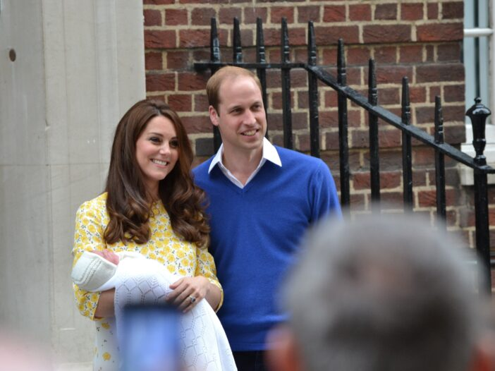 Kate Middleton in a yellow floral outfit holding princess Charlotte in a white blanket with Prince William next to his wife in a blue sweater.
