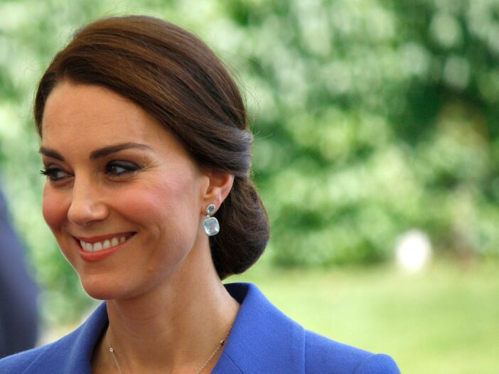 Kate Middleton smiling in a blue outfit