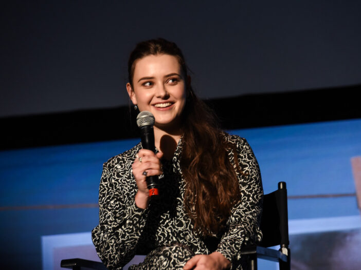 Katherine Langford sitting in a chair holding a mic dressed in a black and white patterned dress