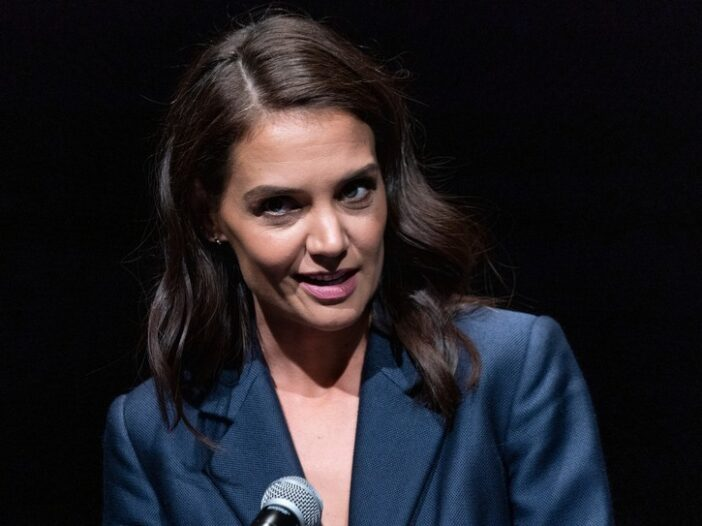 Katie Holmes in a blue blazer, speaking into a microphone.
