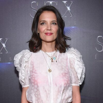 Katie Holmes smiling in a white blouse against a black background