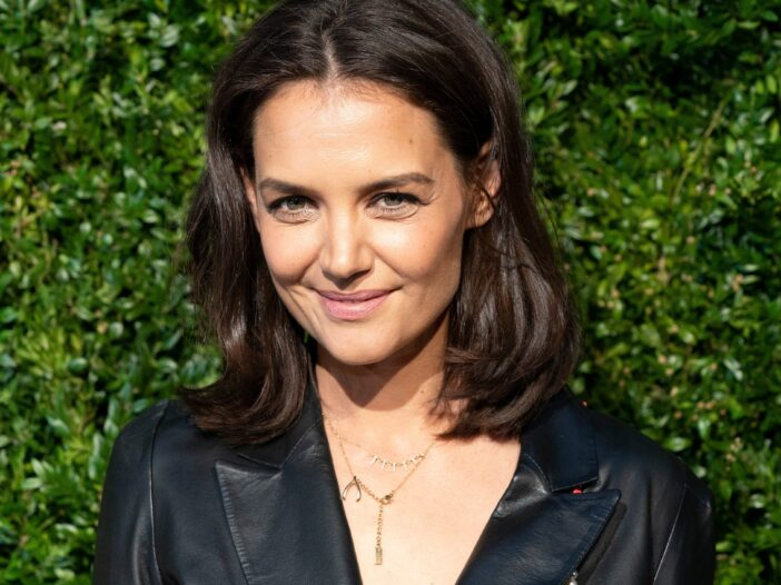 Katie Holmes smiling, wearing a black leather jacket.