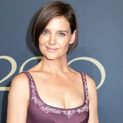 Katie Holmes with short hair and a low-cut purple dress.