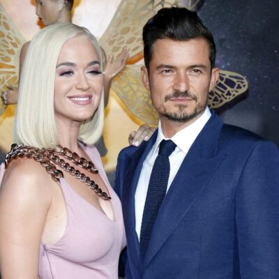 Katy Perry on the left in a pink dress, smiling. Orlando Bloom on the right in a blue suit.