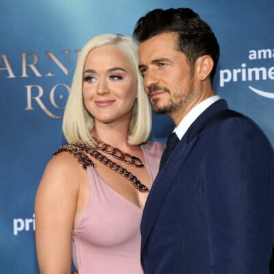 Katy Perry smiles in a light pink dress with Orlando Bloom in a blue suit