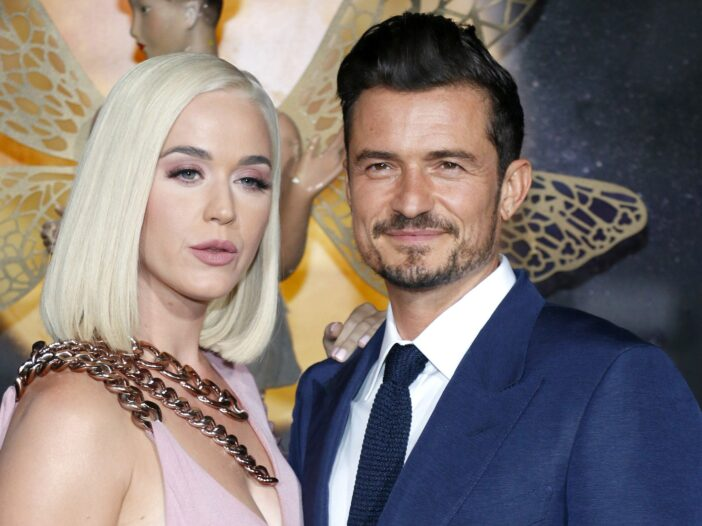 Katy Perry wearing a pale pink dress and standing with Orlando Bloom, in a blue suit