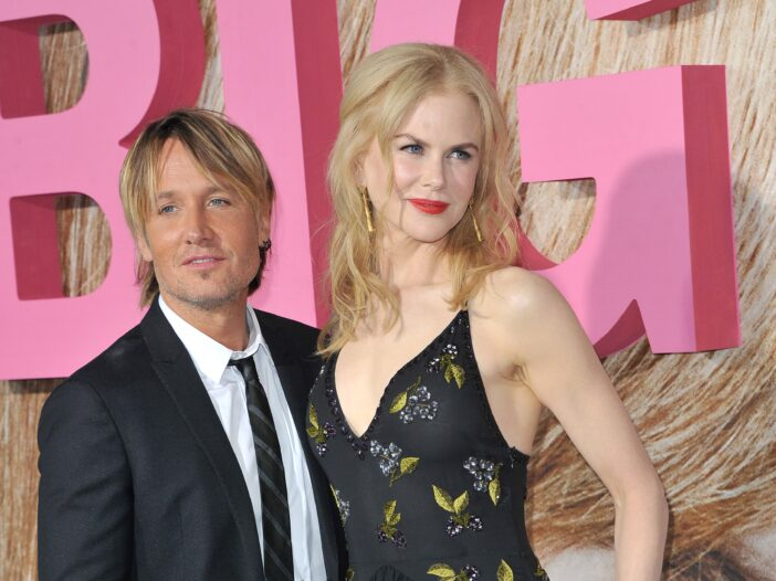Keith Urban, in a black suit, stands with Nicole Kidman, in a black dress, on the red carpet