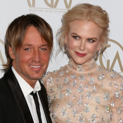 Keith Urban in a black tux standing with Nicole Kidman, wearing a nude-tone dress on the red carpet