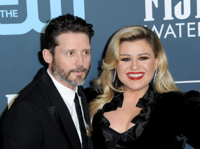 Kelly Clarkson smiling in a black dress with ex husband Brandon Blackstock