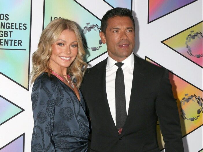 Kelly Ripa smiling in a blue dress with husband Mark Consuelos in a black suit
