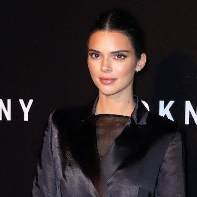 Kendall Jenner in a closed black silk blazer with a black mesh undershirt against a black DKNY backg