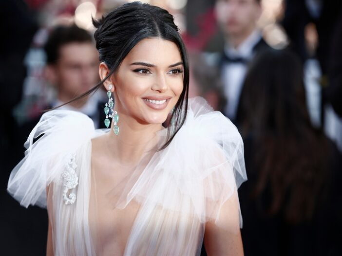 Kendall Jenner in a low-cut, white dress at a red carpet event.