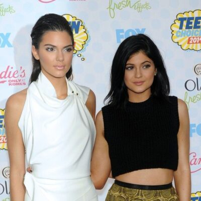 Kendall Jenner in all white standing next to Kylie Jenner in a black top and gold skirt.