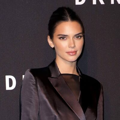 Kendall Jenner looks forward in a closed black jacket against a black background