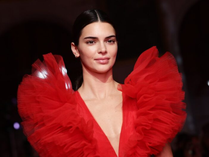 Kendall Jenner smiles wearing a red frilly dress
