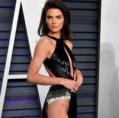Kendall Jenner turned sideways on the red carpet in a slinky black dress