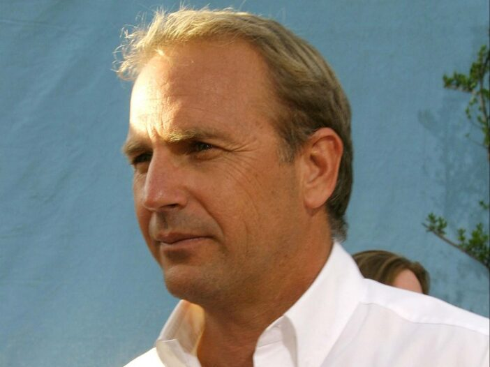 Kevin Costner wearing a casual white, button down shirt at the premiere of Open Range