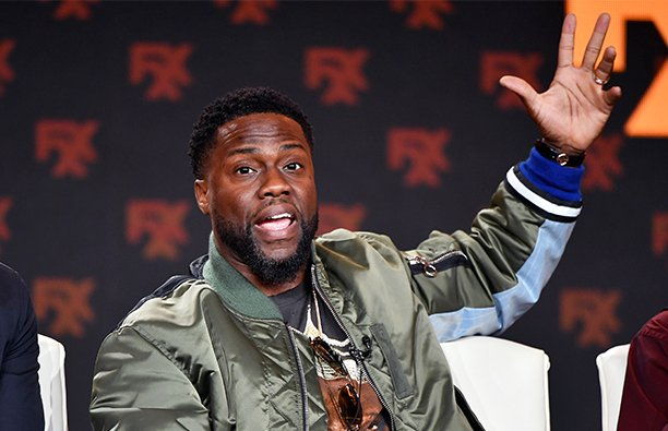 Kevin Hart waving to the crown at a live radio appearance.