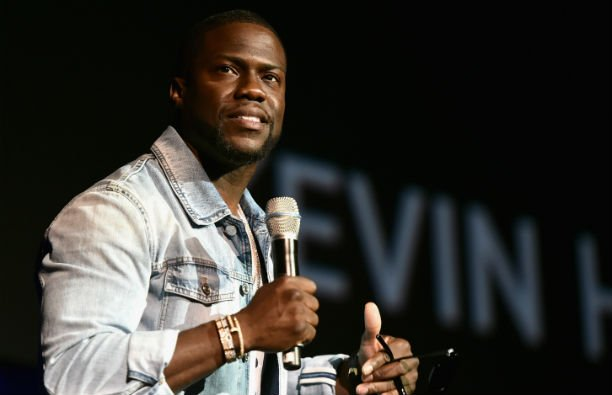 Kevin Hart wearing a denim jacket on stage at CinemaCon 2016