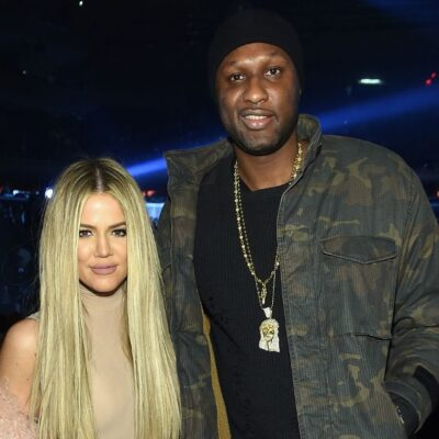 Khloe Kardashian in a beige top standing with Lamar Odom, who's wearing a camouflage jacket, at the