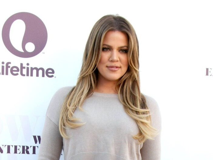 Khloe Kardashian smiling in a tan sweater against a white background