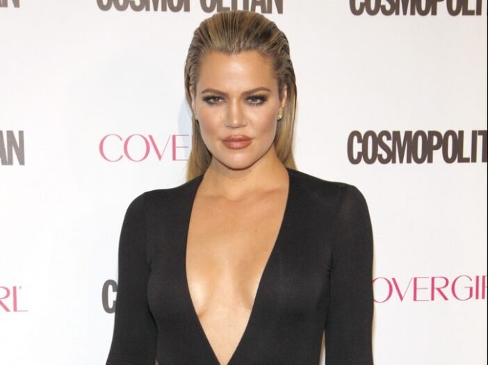Khloe Kardashian wearing a black dress with a plunging neckline on the red carpet