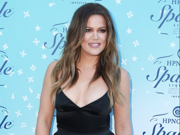 Khloe Kardashian wearing a black jumpsuit at a product launch red carpet