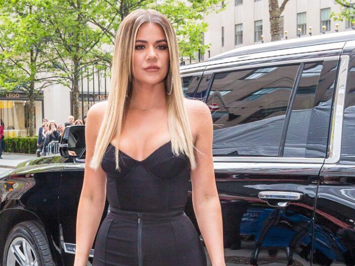 Khloe Kardashian wearing a black outfit, standing on a sidewalk