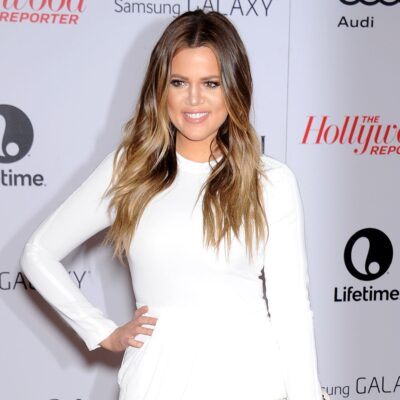 Khloe Kardashian wears a white dress against a white background covered in black lettering