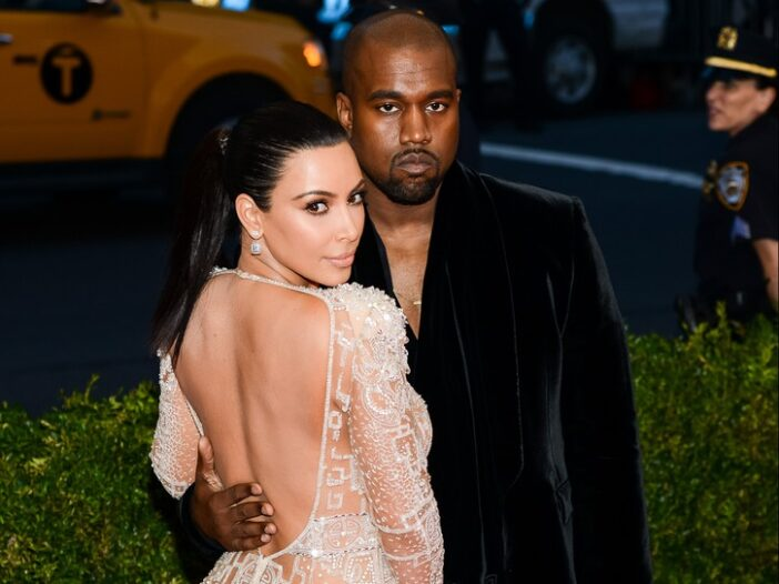Kim Kardashian in a see-through dress standing with Kanye West, in a black suit, at the Met Gala