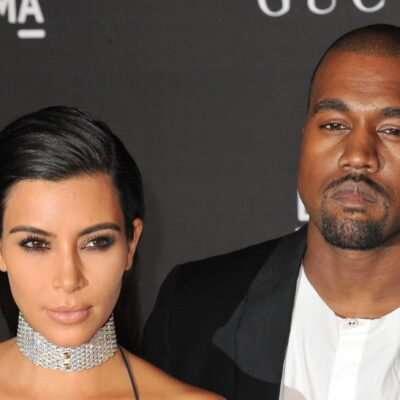 Kim Kardashian on the left wearing a diamond necklace and Kanye West on the right looking annoyed.