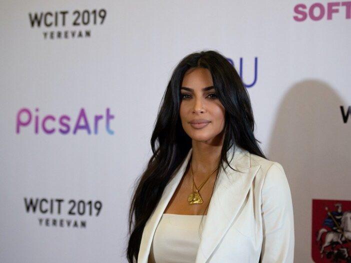 Kim Kardashian smiles in a white pantsuit against a white background