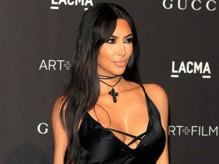 Kim Kardashian smiling in a black laced dress