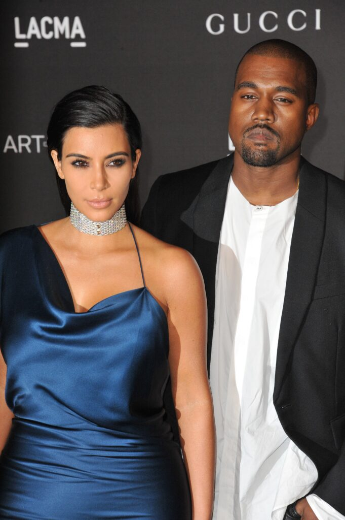 Kim Kardashian wearing a blue dress stands with Kanye West, in a dark blazer, on the red carpet