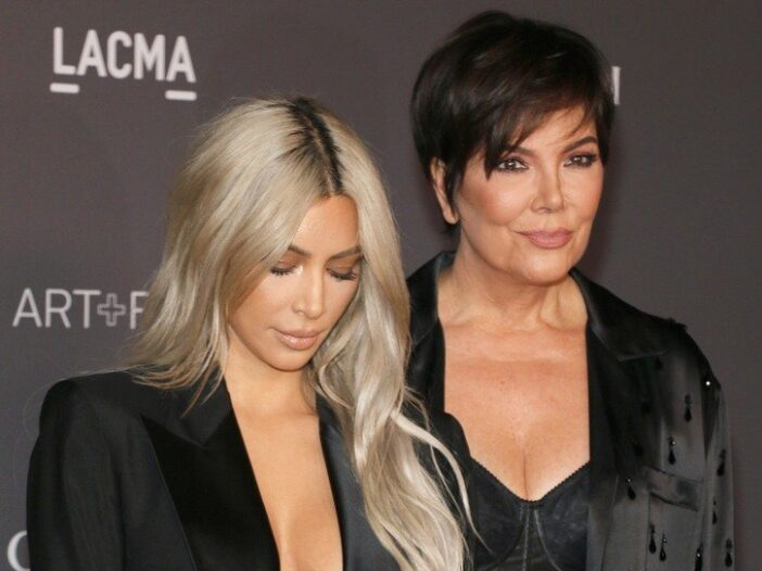 Kim Kardashian wearing an opened black blazer next to her mother, Kris Jenner, also dressed in black