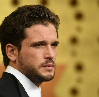 Kit Harington wearing a black suit on the red carpet.