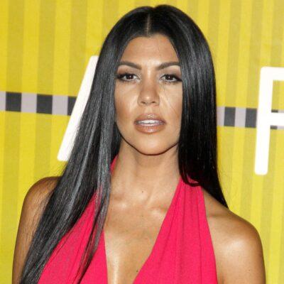 Kourtney Kardashian wearing a bright red jumpsuit at the MTV Movie Awards