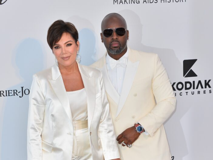 Kris Jenner and Corey Gamble in white suits.