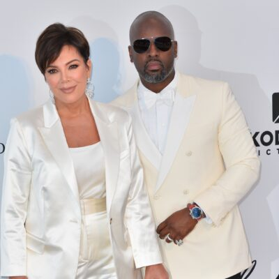 Kris Jenner and Corey Gamble, both wearing white suites, pose together on the red carpet