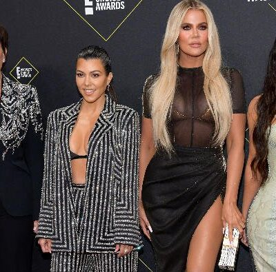 Kris Jenner in black suit, Kourtney Kardashian in pin-stripe suit, Khloe Kardashian in black dress,