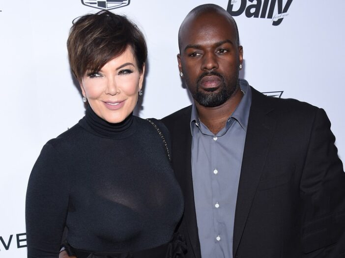 Kris Jenner, wearing all black, poses with Corey Gamble, who's wearing a black blazer