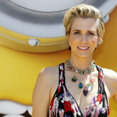 Kristen Wiig smiles in a multicolored dress against a yellow background