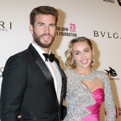 Liam Hemsworth in a tuxedo smiles with Miley Cyrus in a silver-pink dress